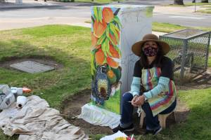 artist sits close to the ground near their half finished utility box painting.
