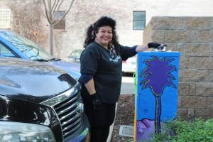 Female artist smiles at photographer as they rest their arm over a newly painted utility box. The artwork painted on the box is of cool tone colors and shows a palm tree with the mountains in the background.