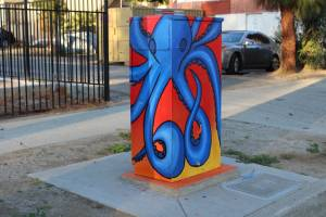 Utility box painted with a red and yellow ombre, and a bright blue, octopus on top.
