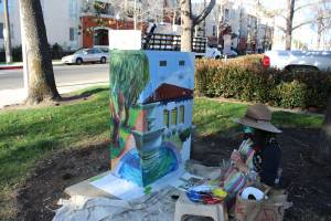 Artist wears wide brimmed hat and sits on blanket as they paint a utility box.